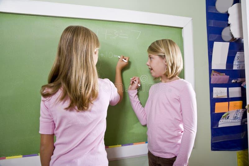 Niños que escriben en la pizarra en sala de clase imagen de archivo
