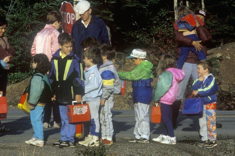 Niños que esperan para subir al autobús escolar imágenes de archivo libres de regalías