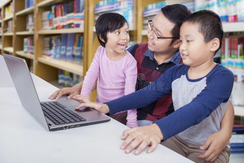 Niños que estudian con el padre y el ordenador portátil en biblioteca fotos de archivo libres de regalías