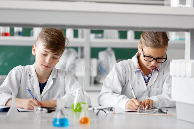 Niños que estudian química en el laboratorio de la escuela fotografía de archivo libre de regalías
