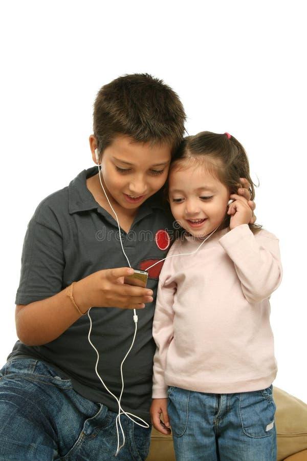 Niños que gozan de un jugador mp4 foto de archivo