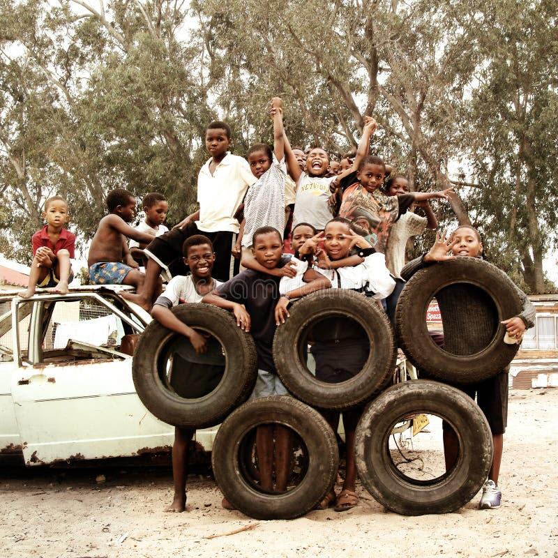 Niños que hacen círculos olímpicos con los neumáticos en el municipio, Suráfrica fotografía de archivo libre de regalías