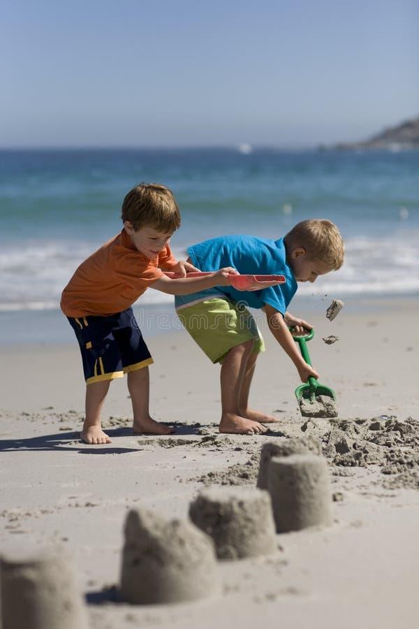 Niños que hacen castillos de la arena foto de archivo