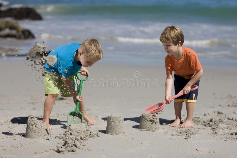 Niños que hacen castillos de la arena foto de archivo libre de regalías