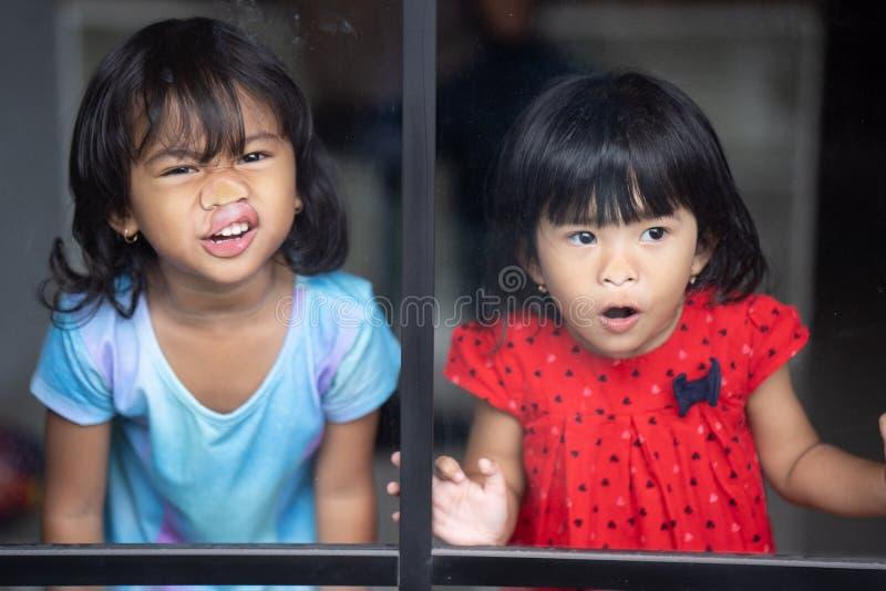 Niños que hacen la cara guarra contra ventana fotos de archivo