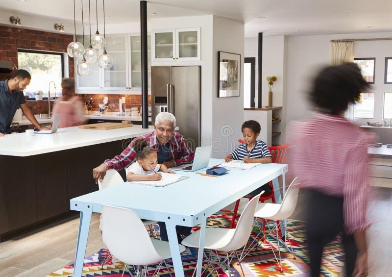 Niños que hacen la preparación en domicilio familiar multi ocupado de la generación foto de archivo
