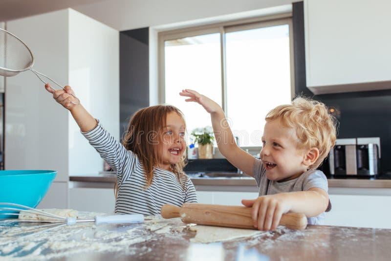 Niños que hacen las galletas y que se divierten en la cocina imagen de archivo