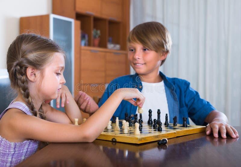 Niños que juegan a ajedrez en casa imagen de archivo libre de regalías