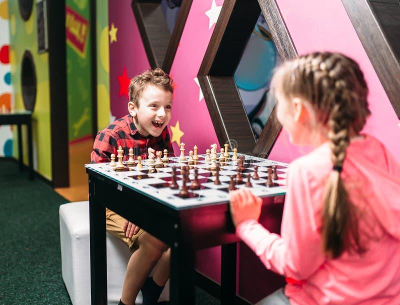Niños que juegan a ajedrez en centro de entretenimiento fotografía de archivo