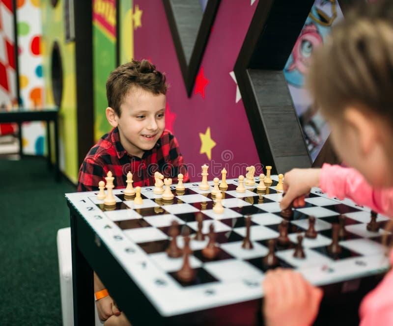 Niños que juegan a ajedrez en centro de entretenimiento imagenes de archivo