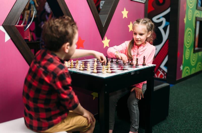 Niños que juegan a ajedrez en centro de entretenimiento imagen de archivo