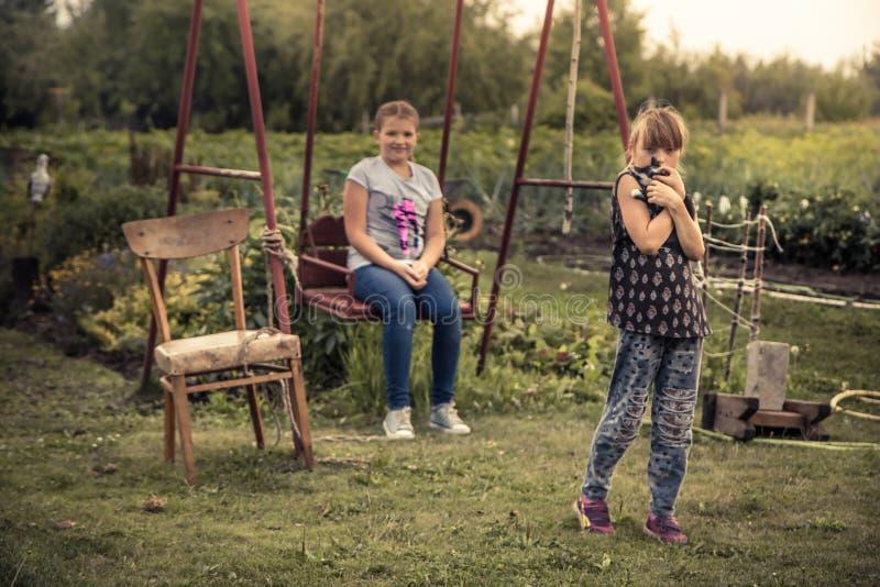 Niños que juegan al aire libre forma de vida del campo del patio del patio trasero durante vacaciones de verano en los niños feli fotos de archivo libres de regalías