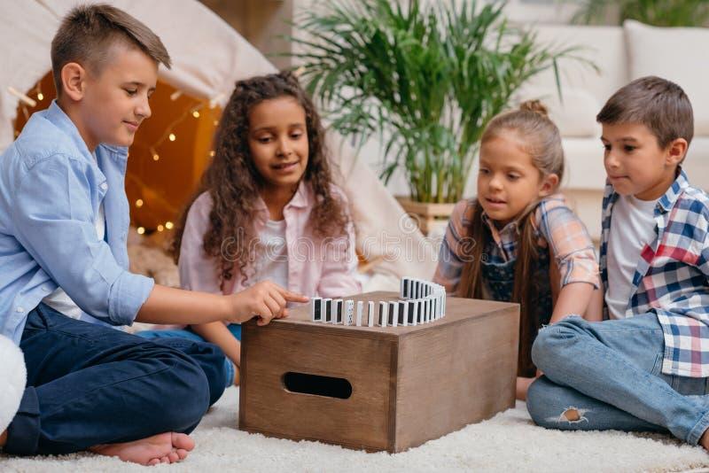 Niños que juegan al juego del dominó junto en casa fotografía de archivo