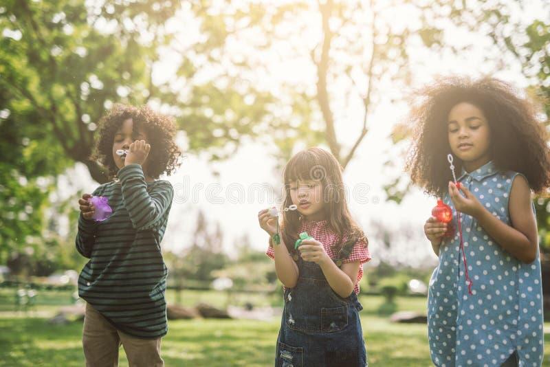 Niños que juegan burbujas que soplan juntas en el campo fotografía de archivo