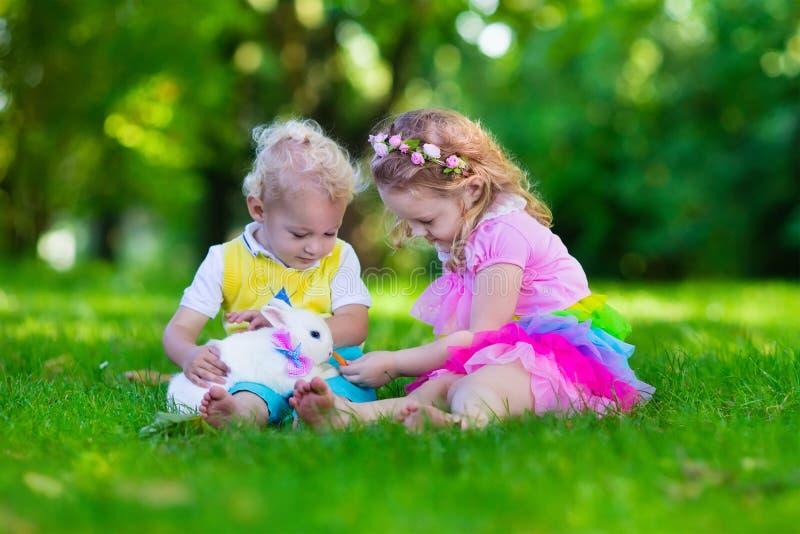 Niños que juegan con el conejo del animal doméstico imagen de archivo