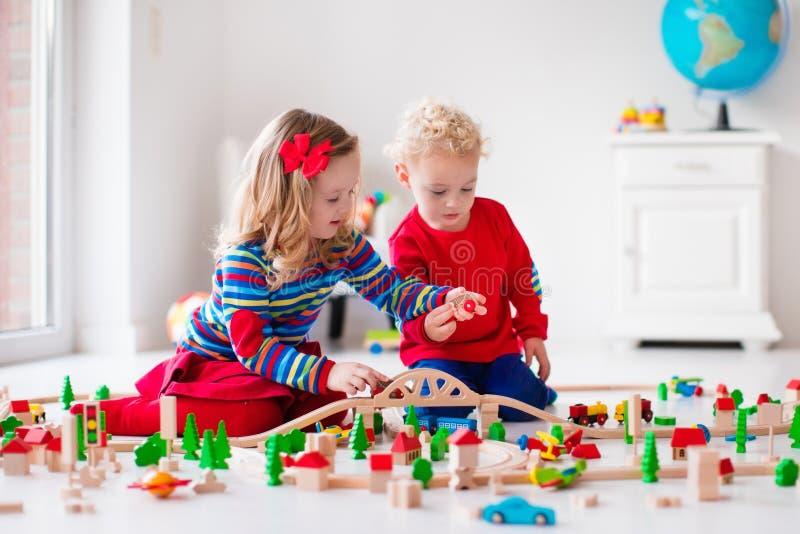 Niños que juegan con el ferrocarril y el tren del juguete fotografía de archivo
