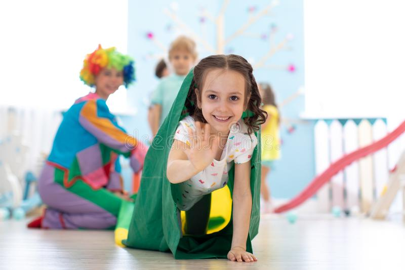 Niños que juegan con el payaso en fiesta de cumpleaños en centro de entretenimiento foto de archivo libre de regalías