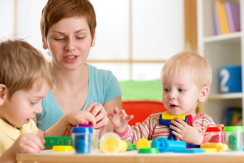 Niños que juegan con la arcilla del juego en casa, la guardería o el playschool fotos de archivo