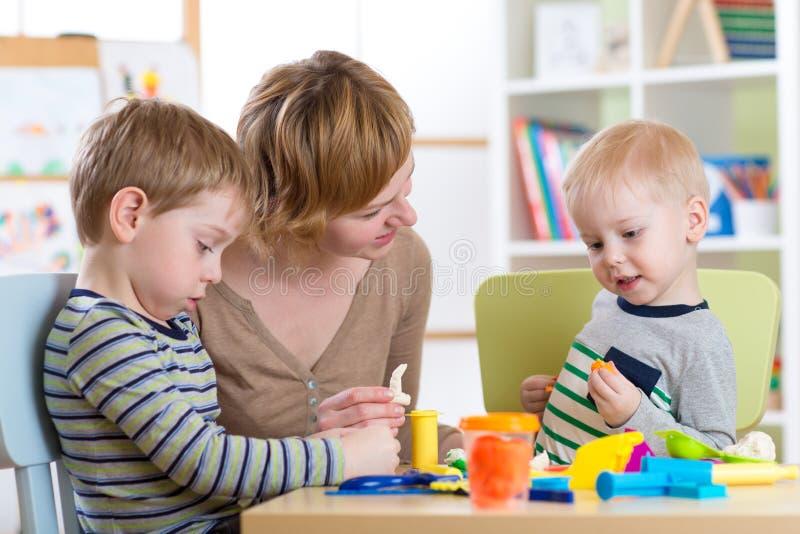 Niños que juegan con la arcilla del juego en casa o guardería o playschool imagenes de archivo