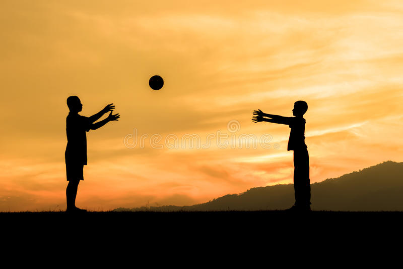 Niños que juegan con la bola en el prado, puesta del sol foto de archivo libre de regalías