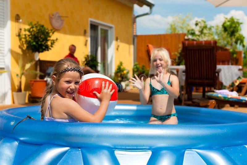 Niños que juegan con la bola en piscina de agua fotografía de archivo