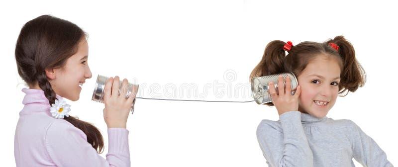 Niños que juegan con la lata y el teléfono de la secuencia foto de archivo libre de regalías