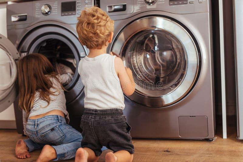 Niños que juegan con la lavadora en casa fotos de archivo