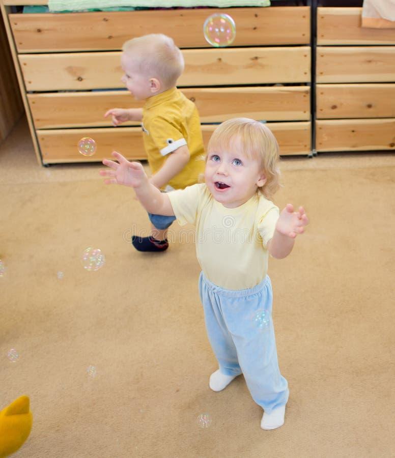 Niños que juegan con las burbujas de jabón en centro de cuidado de día fotografía de archivo