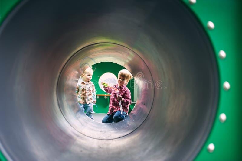 Niños que juegan con las burbujas en el patio fotos de archivo