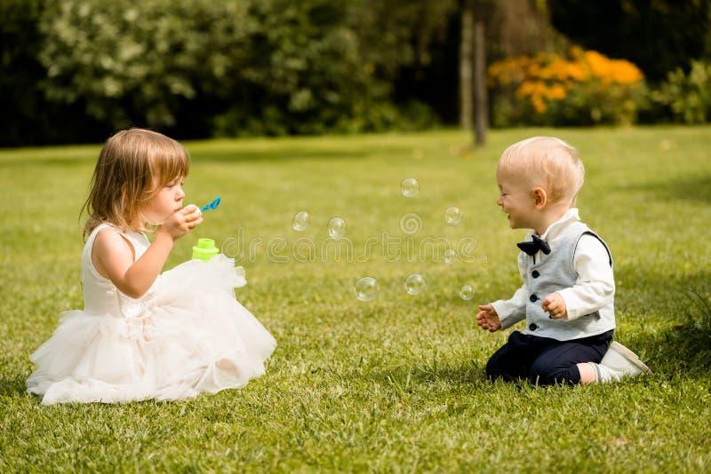 Niños que juegan con las burbujas en parque del verano fotografía de archivo