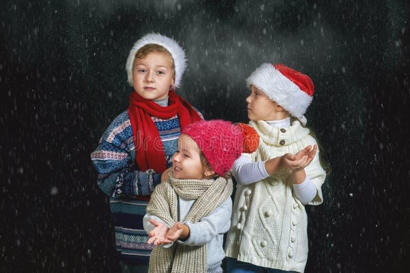 Niños que juegan con los copos de nieve en un fondo oscuro imagen de archivo libre de regalías