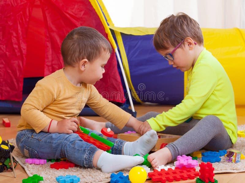 Niños que juegan con los juguetes coloreados fotos de archivo libres de regalías