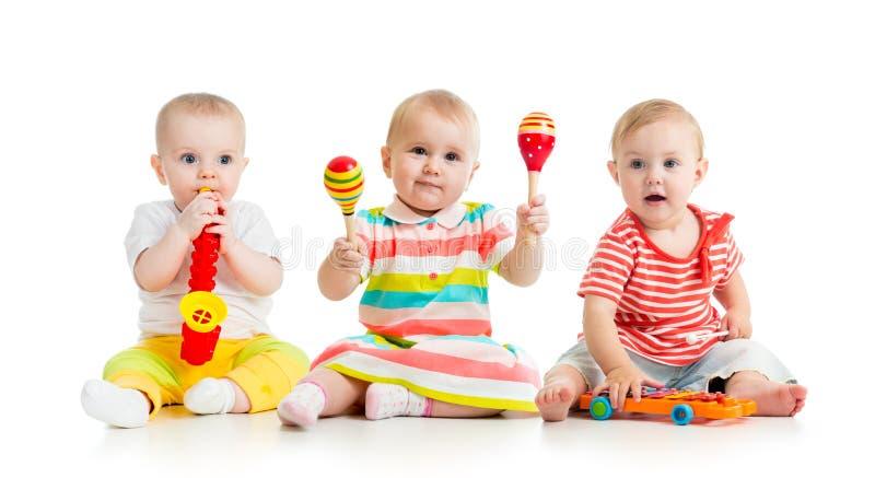 Niños que juegan con los juguetes musicales Aislado en el fondo blanco imagenes de archivo