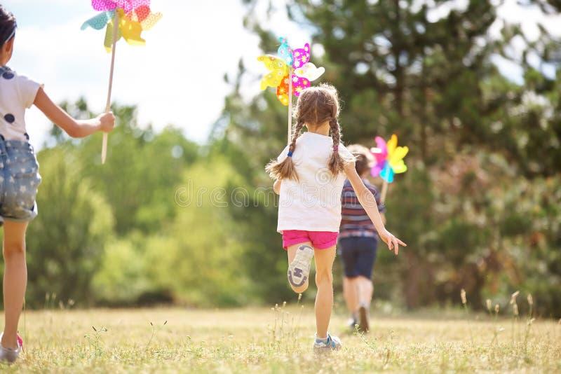 Niños que juegan con los molinillos de viento imagen de archivo libre de regalías