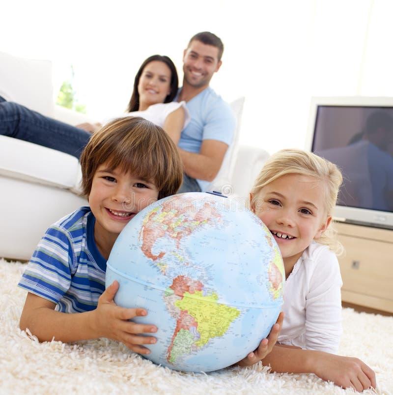 Niños que juegan con un globo terrestre fotografía de archivo