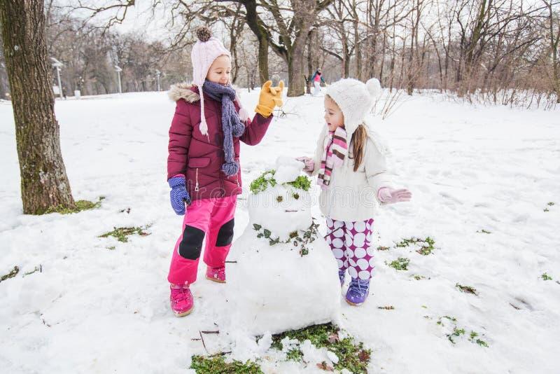 Niños que juegan con un muñeco de nieve en el parque en el día de invierno imagenes de archivo