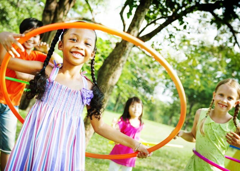 Niños que juegan concepto alegre del ejercicio del aro fotografía de archivo