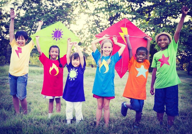Niños que juegan conceptos de la amistad de la vinculación de la cometa fotografía de archivo