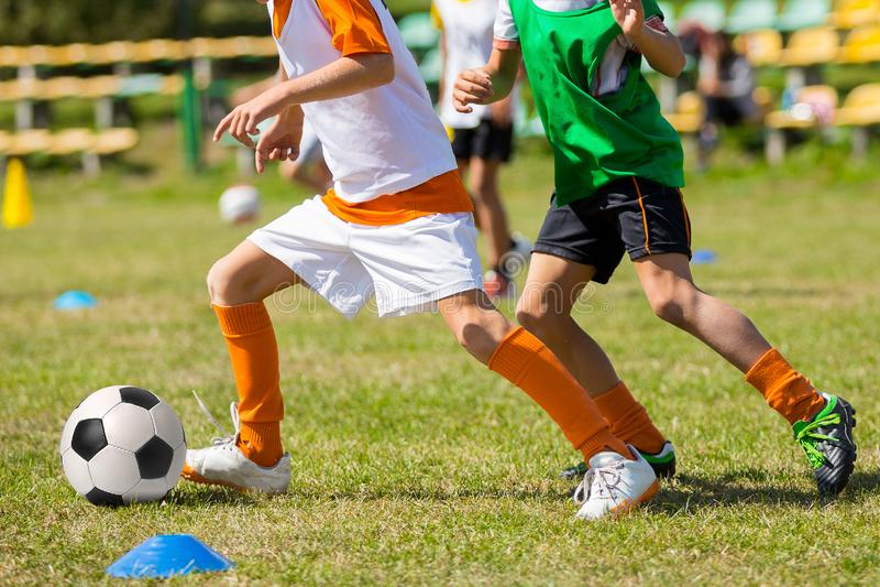 Niños que juegan el balón de fútbol en campo de hierba Competencia del fútbol entre dos niños imagenes de archivo
