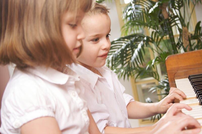 Niños que juegan el piano imagenes de archivo
