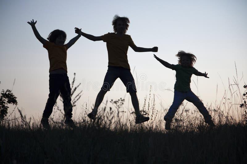 Niños que juegan el salto en el prado de la puesta del sol del verano silueteado fotografía de archivo libre de regalías