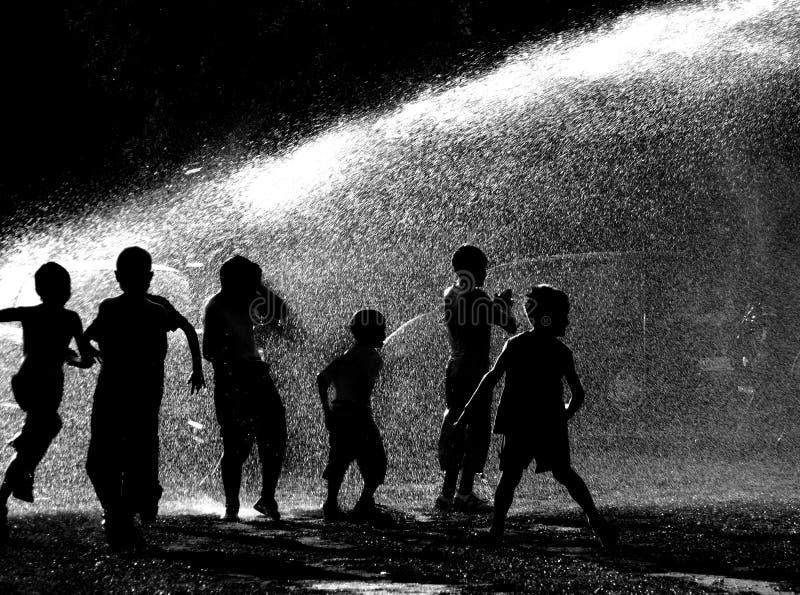 Niños que juegan en agua fotos de archivo
