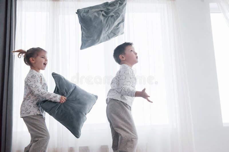 Niños que juegan en cama de los padres Los niños despiertan en dormitorio blanco soleado Juego del muchacho y de la muchacha en p imagenes de archivo