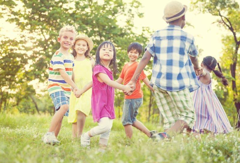 Niños que juegan en el concepto de la felicidad del parque fotografía de archivo
