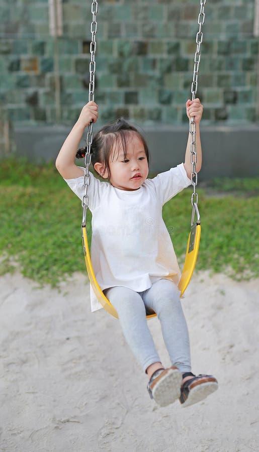 Niños que juegan en el oscilación en el patio fotos de archivo