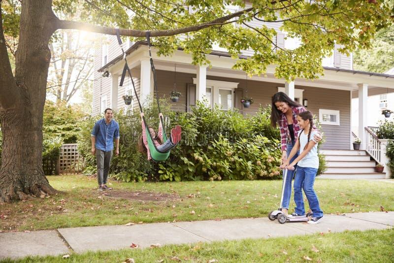 Niños que juegan en el oscilación y la vespa del jardín fuera de la casa fotografía de archivo libre de regalías