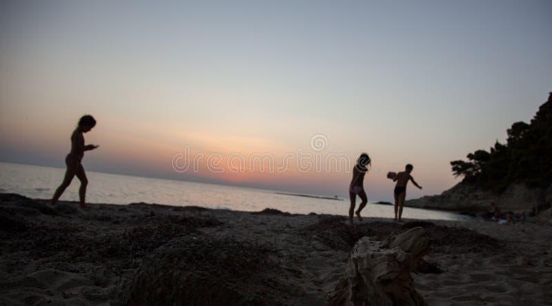 Niños que juegan en el prado de la puesta del sol del verano, el jugar feliz de los niños imágenes de archivo libres de regalías