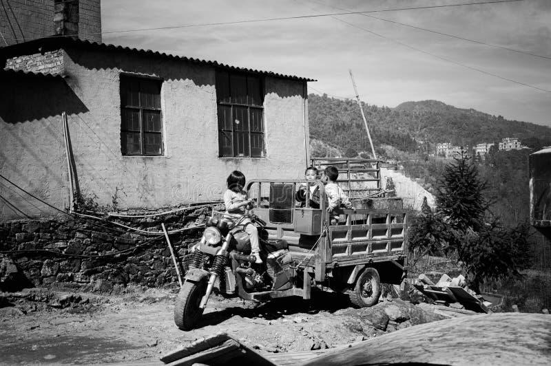 Niños que juegan en el tractor cerca de un edificio abandonado imagen de archivo