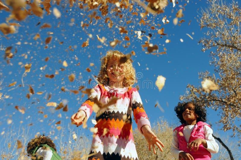 Niños que juegan en hojas imagen de archivo