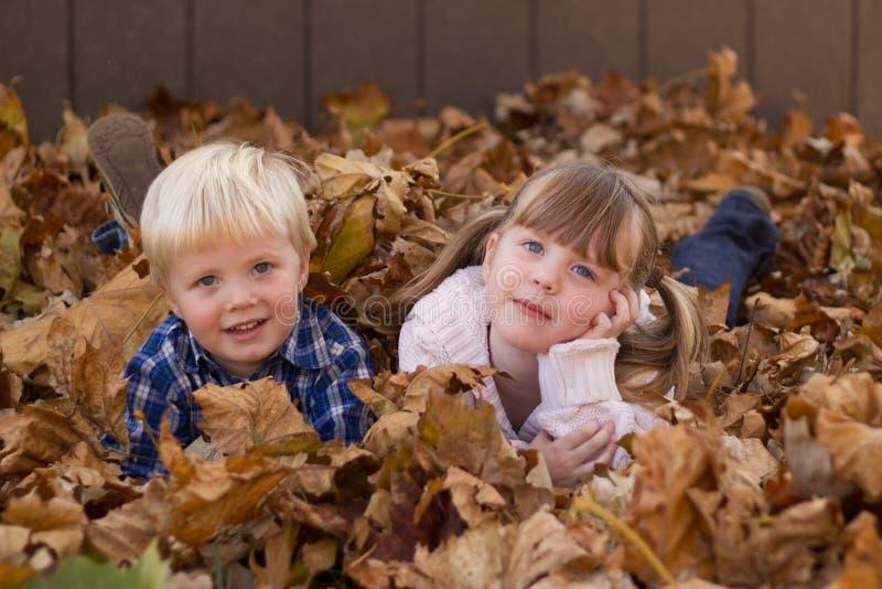 Niños que juegan en hojas de la pila de la hoja imágenes de archivo libres de regalías
